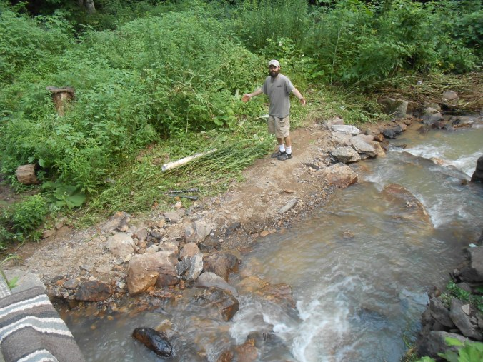 """My husband, Nathan, standing on our new """"beach""""..before the flooding happened there were several huge boulders there"""