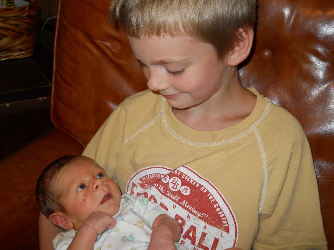 My oldest son, Elijah, cradling my youngest son, Samuel, who is only a few days old