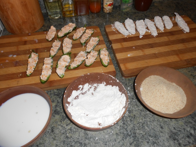 dip the stuffed pepper half in the milk the roll in the flour, this works best when you designate and hand to each job...left hand for milk, right hand for flour/breadcrumbs.  Otherwise you wet with milk hand will get all gummed up with flour and breadcrumbs and require frequent washings (...again, I have learned this the hard way on more than one occasion...)